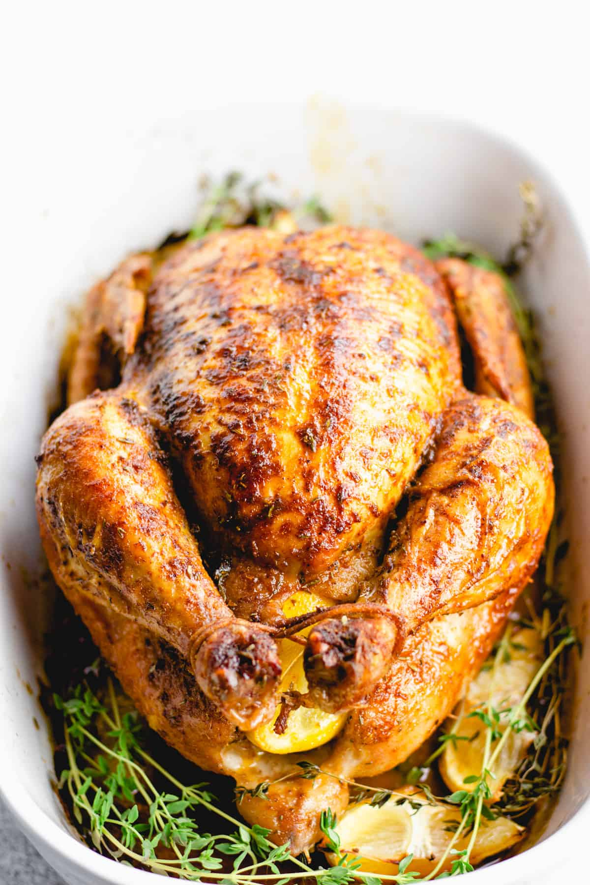 A cooked whole roasted chicken placed in a white baking pan with thyme and lemon wedges.