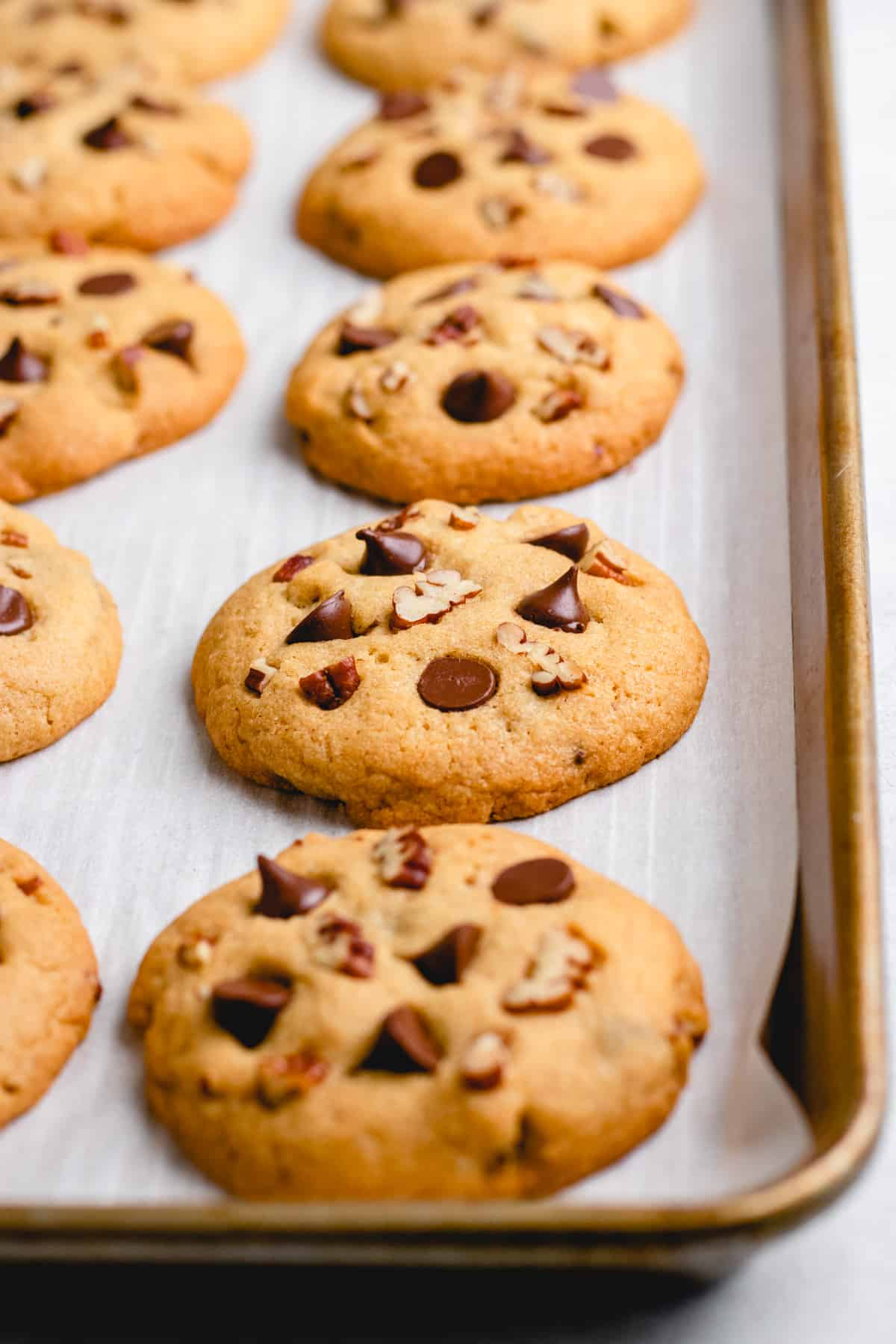 Pecan Chocolate Chip Cookies on a baking sheet with parchment paper.