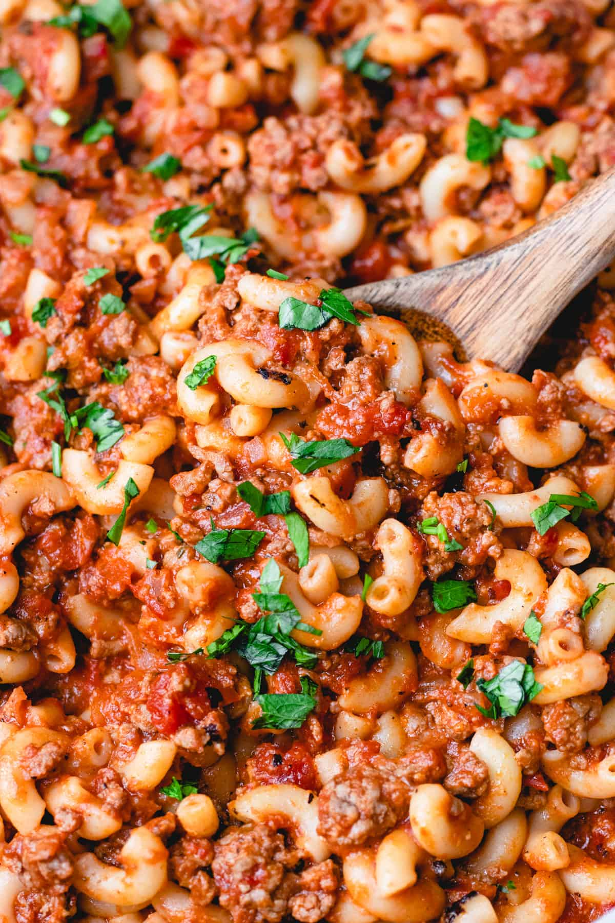 Old Fasioned American Goulash, made with round beef, tomato sauce, and elbow macaroni, topped with chopped parsley.
