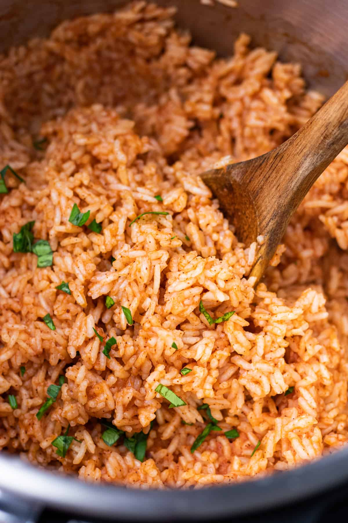 Mexican rice in instant pot, with a wooden spoon and chopped parsley.