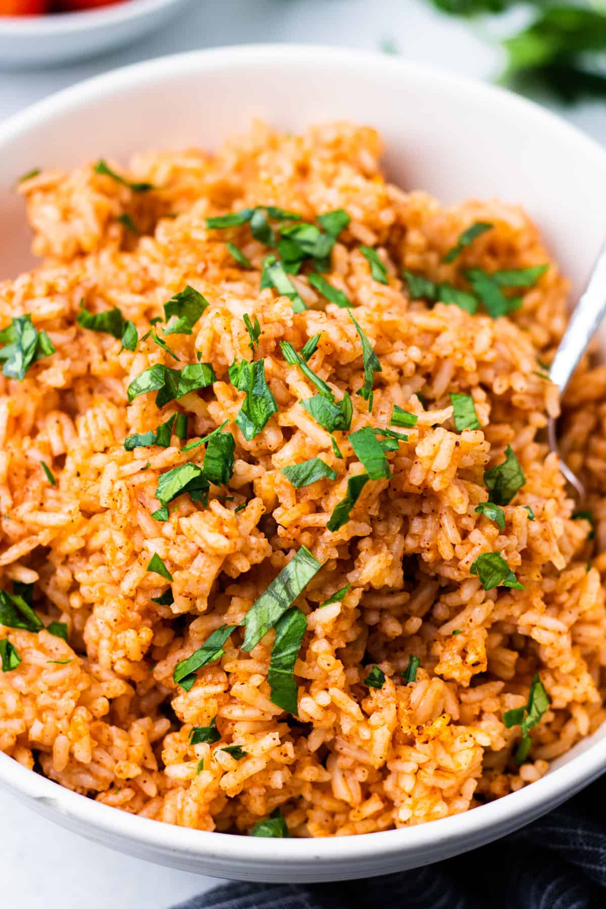 Mexican rice in a bowl with a spoon and chopped parsley.